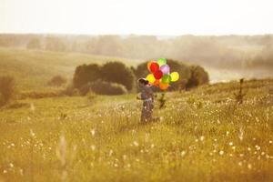 gelukkig meisje met ballonnen die op het veld rennen foto