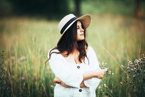 mooie vrouw in een strohoed tussen het gras van het veld foto