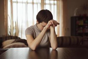 mooie jonge vrouw zit en verdrietig foto