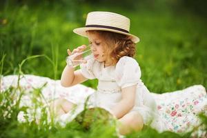 klein meisje zit en drinkt foto