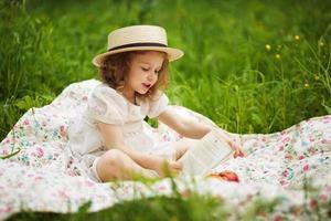 klein meisje zitten en lezen foto