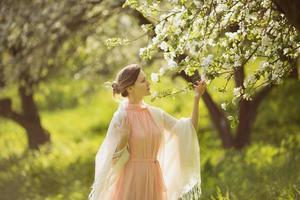 gelukkige vrouw in de buurt van de bloeiende appelboom foto