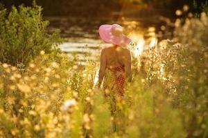 vrouw met hoed aan de waterkant op een zomeravond foto