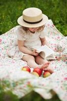 klein meisje zit en leest een boek foto