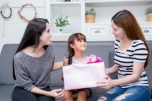 gelukkige familie, moeder en dochter geven geschenkdoos met dochter. foto