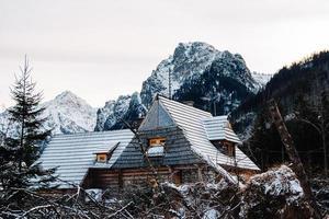 houten huis in de bergen bedekt met verse sneeuw in de winterbergen foto