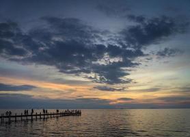 toeristen bekijken zonsondergang bij de pier in Kep Town aan de kust van Cambodja foto