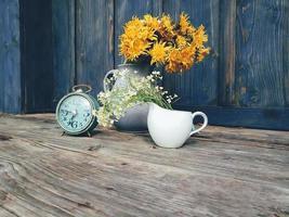 gele bloemen en klok op blauwe rustieke achtergrond foto