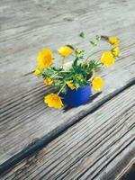 gele verse wilde bloemen in blauwe keramische vaas, op houten veranda achtergrond. stilleven in rustieke stijl. close-up bekijken. lente of zomer in de tuin, platteland lifestyle concept. kopieer ruimte foto