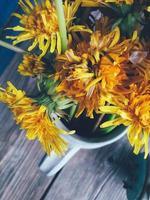gele paardebloembloemen in kleikruik, grote en verse hoofden, op houten achtergrond. bovenaanzicht close-up afbeelding. levendige kleuren. plattelandslevensstijl, vakantie, vakantieconcept foto