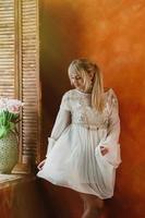 jonge blonde vrouw in witte jurk dansen bij het raam, verse roze bloemen boeket in mooie vaas, heldere sienna muur op de achtergrond. romantisch, liefde, geluk concept foto