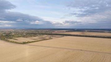 luchtfoto van graanvelden na de oogst met hooiberg foto