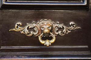 antieke deurknop in de vorm van een koperen leeuw foto