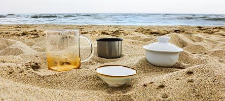kust. gerechten met thee op het zand. zomervakantie. foto