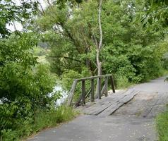 staande oude houten brug over rivier in gekleurde achtergrond foto
