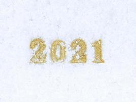 nieuwjaar 2021 cijfers op witte sneeuw textuur achtergrond. foto