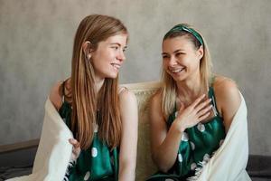 twee lachende jonge vrouwen die plezier hebben wanneer ze zich verstoppen onder een witte deken foto