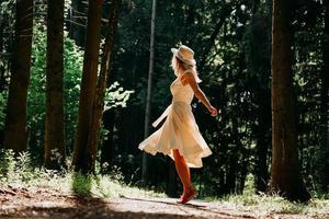 een jonge vrouw in een witte jurk en een strohoed loopt door het bos foto