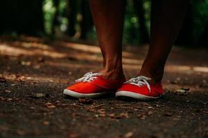 benen in rode sneakers op een herfstpad in het park. zwarte leren poten foto