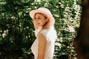 mooie jonge vrouw in een strohoed en witte jurk in een groen park foto