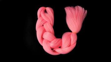 roze kanekalon hangt op een zwarte achtergrond foto