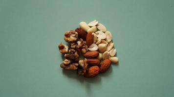 een handvol noten op felgroene achtergrond, gekleurde achtergrond foto
