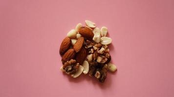 een handvol noten op felroze achtergrond, gekleurde achtergrond foto