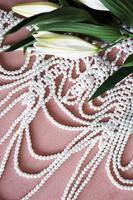 witte lelies en een ketting van parels op een roze achtergrond. foto