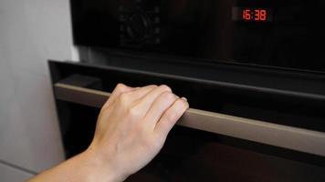 close-up van vrouwenhand die de ovendeur opent om het gebraad te regelen foto