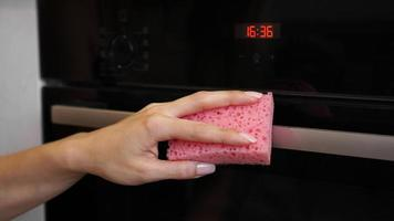 de oven buiten schoonmaken. een vrouwelijke hand maakt ovenpaneel schoon foto