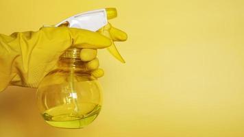 hand in gele rubberen handschoen met plastic spray foto