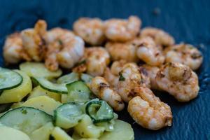 pittige witte tijgergarnalen van de grill met aardappel-komkommersalade foto