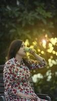 jonge vrouw in een gebloemde jurk die een kopje koffie drinkt foto