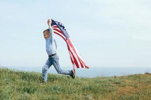 een kleine jongen rent met de vlag van de verenigde staten foto