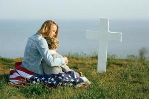 moeder en zoon zitten op het graf van een soldaat foto