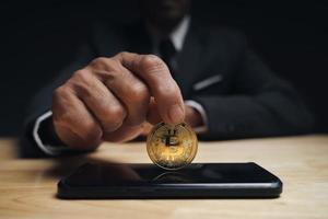zakenman houdt gouden bitcoin op smartphone vast voor bitcoin-handel. foto