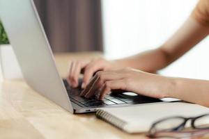 vrouw die op laptop toetsenbord typt foto