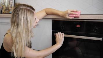 jonge vrouw die oven in de keuken schoonmaakt. foto