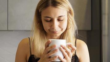 close-up van een vrouw die de geur van koffie inademt met haar ogen dicht foto