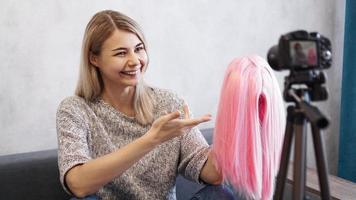 vrouw blogger neemt video op. ze toont roze pruik foto