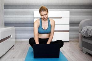 meisje traint thuis en kijkt naar video's op laptop, training foto
