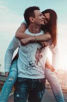 gelukkige man die zijn vriendin draagt op de achtergrond van de zonsondergang foto
