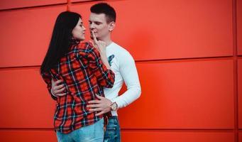 paar daten en verliefd knuffelen op een zonnige dag - rode achtergrond foto