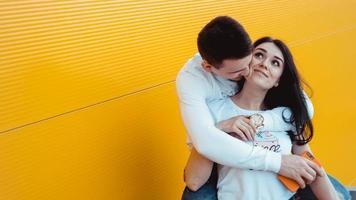 jonge mooie paar poseren samen en knuffelen over gele achtergrond foto