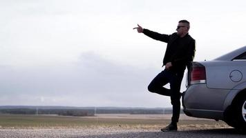 sde weergave van zakenman in bril zittend op auto kofferbak foto