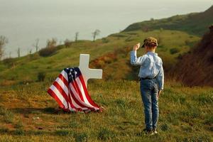 jonge jongen met een militaire pet groet het graf van zijn vader foto