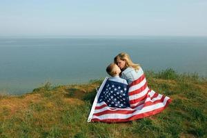 vrouw en haar kind lopen met de Amerikaanse vlag aan de oceaankust foto
