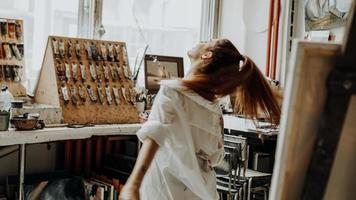 mooie vrouwelijke schilder die danst tijdens het schilderen in een kunstatelier foto