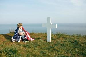 een jonge jongen met een militaire pet, bedekt met de vlag van de VS foto