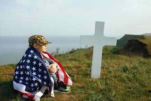 jonge jongen met een militaire pet bij het graf van zijn vader op herdenkingsdag foto